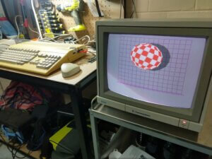 An Amiga 500 on a bench attached to a monitor running the classic bouncing ball demo